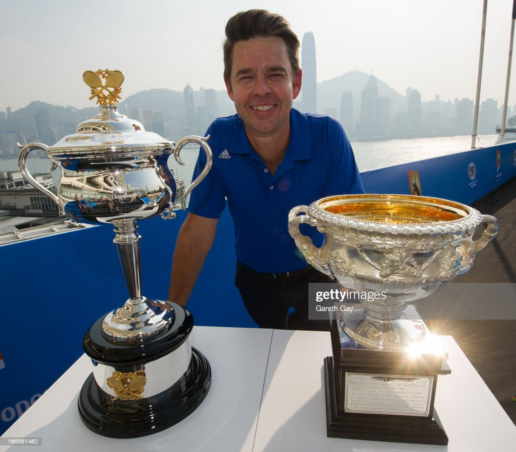 Todd Woodbridge poses for the press, with the AO trophys over looking the Hong Kong skyline during the Australian Open Trophy tour on October 22, 2013 in Hong Kong, Hong Kong.