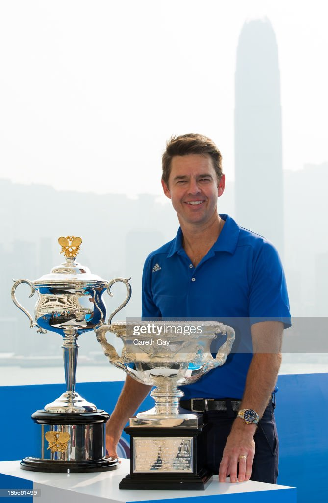 Todd Woodbridge poses for the press with the AO trophys over looking the Hong Kong skyline during the Australian Open Trophy tour on October 22, 2013 in Hong Kong, Hong Kong.