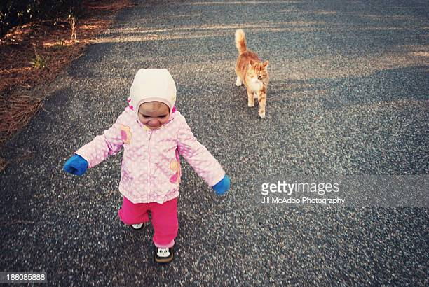 toddler and cat walking