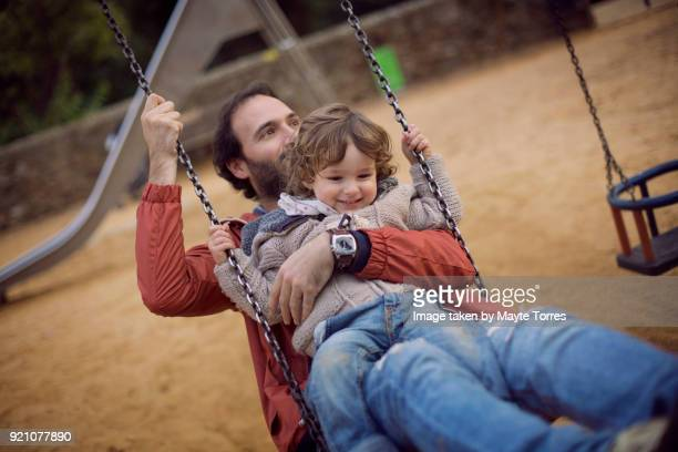 toddler and dad having fun in the swing together - padre soltero fotografías e imágenes de stock