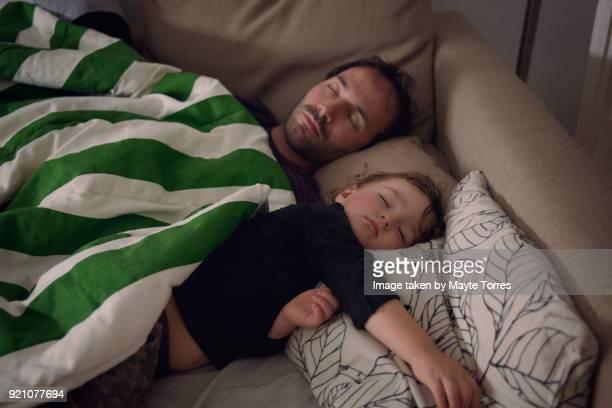 Toddler and dad take a nap in the sofa