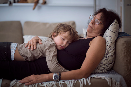 Toddler and grandma taking a nap in sofa - gettyimageskorea