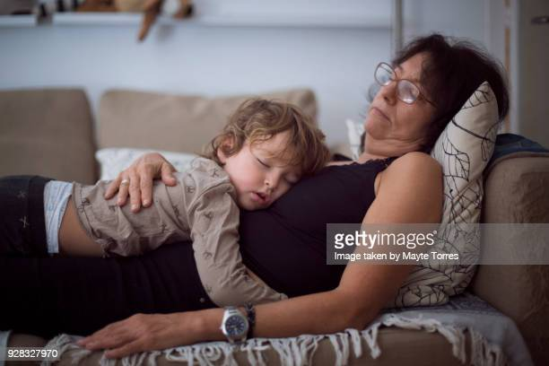 toddler and grandma taking a nap in sofa - zakenman stock pictures, royalty-free photos & images