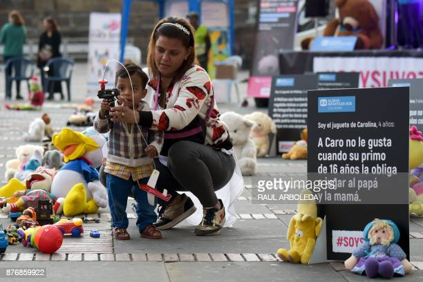 A toddler and his mother are pictured during an urban intervention at Bolivar square in Bogota to protest against child abuse and to raise awareness...