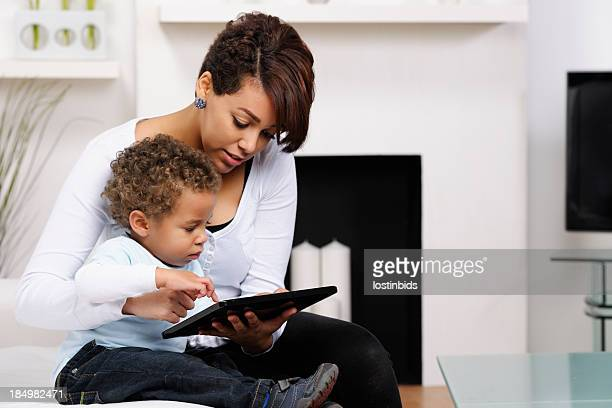 Toddler And Young Mother/ Sister Using A Digital Tablet