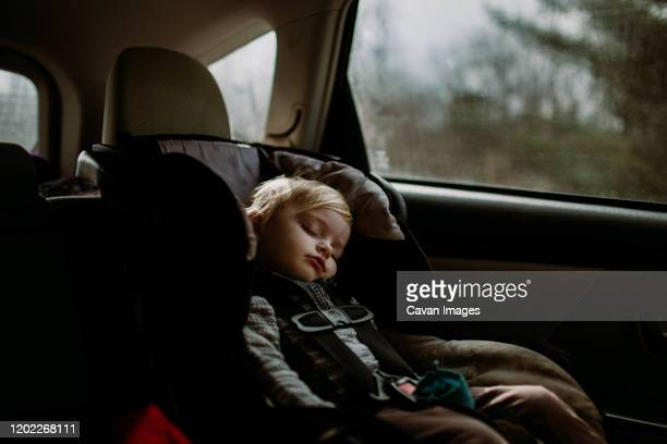 toddler asleep in carseat on road trip - land vehicle stock pictures, royalty-free photos & images