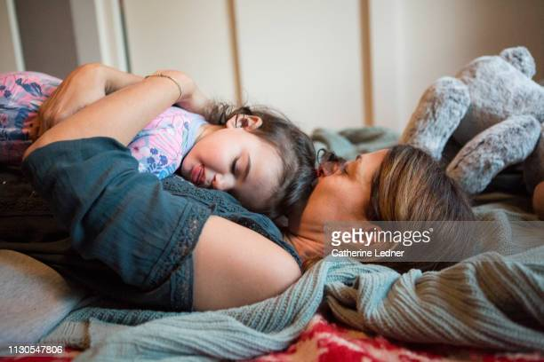 Toddler asleep on mom's chest as they both lie down