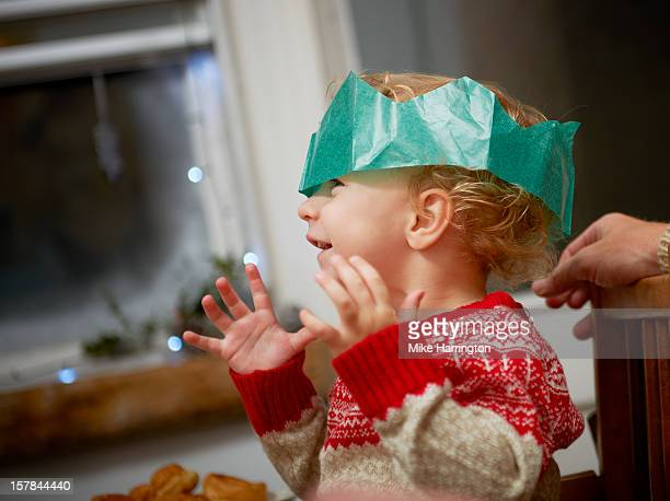 Toddler at Christmas dinner wearing paper hat.