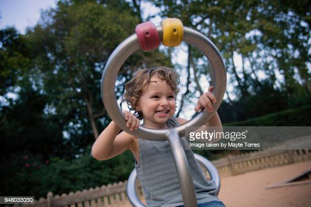 Toddler at playground playing with a metal structure