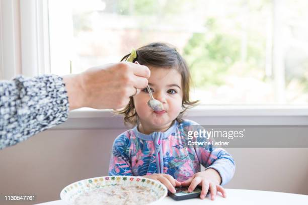 Toddler at table being fed oatmeal