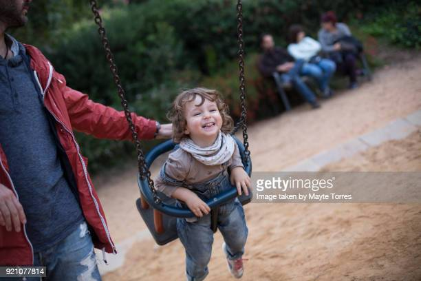 Toddler at the swing while dad pushes and people sit on a bench