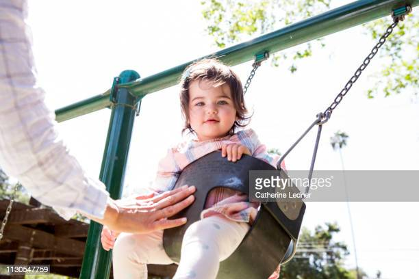 toddler being swung in a bucket swing at the park