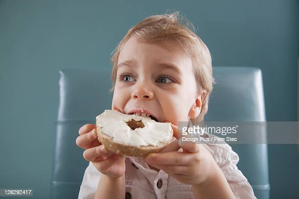 toddler biting a bagel with cream cheese