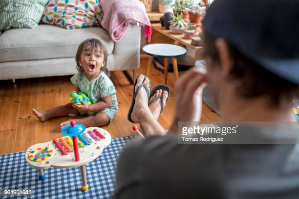 Toddler boy and dad in the living room with a xylophone