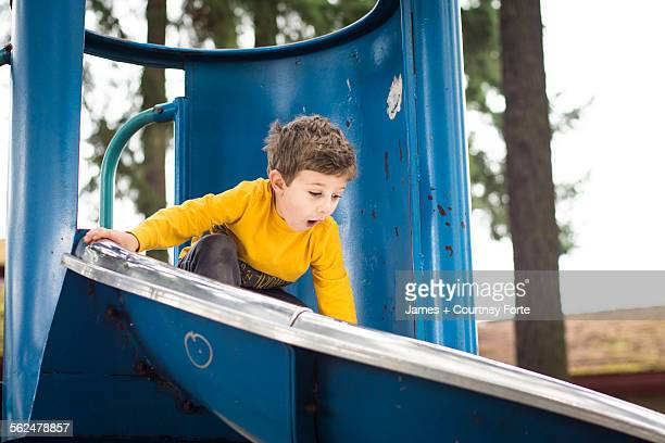 Toddler boy anticipates a steep slide at the playground, Portland, Oregon.