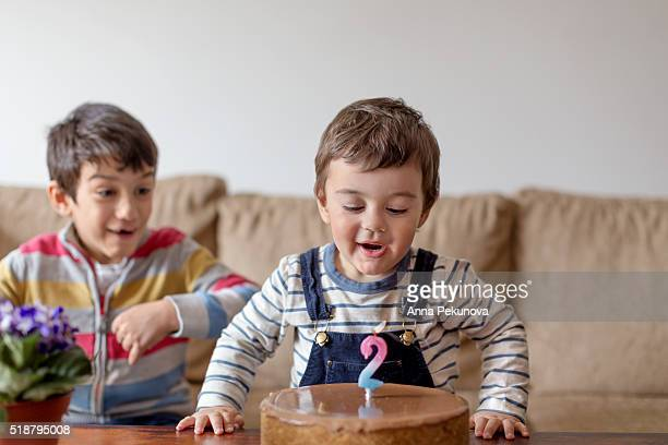 Toddler boy blowing out birthday candles together with older brother