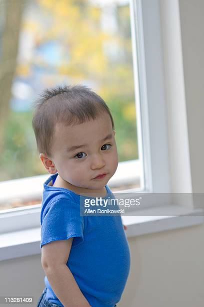 toddler boy by bright window full of outside color