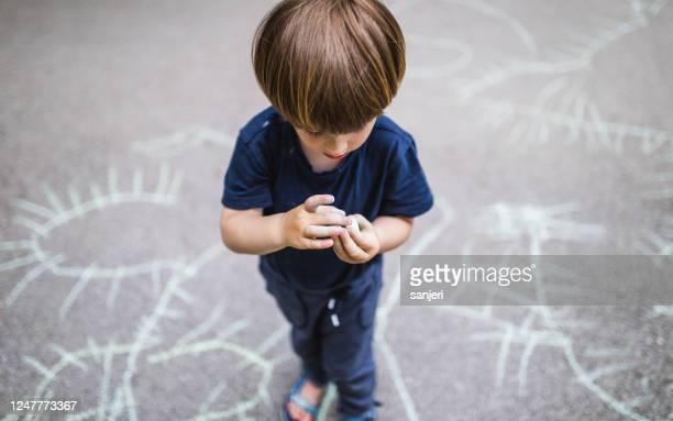 de jongen die van de peuter op de straat krijtt - alleen één jongen stockfoto's en -beelden