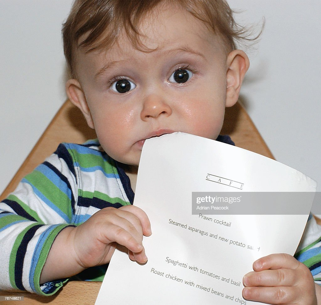 Toddler boy chewing on a menu : Stock Photo