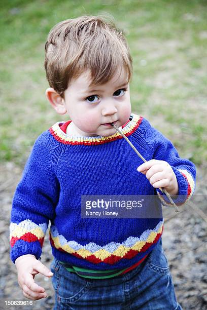 Toddler boy chewing on stick outdoors