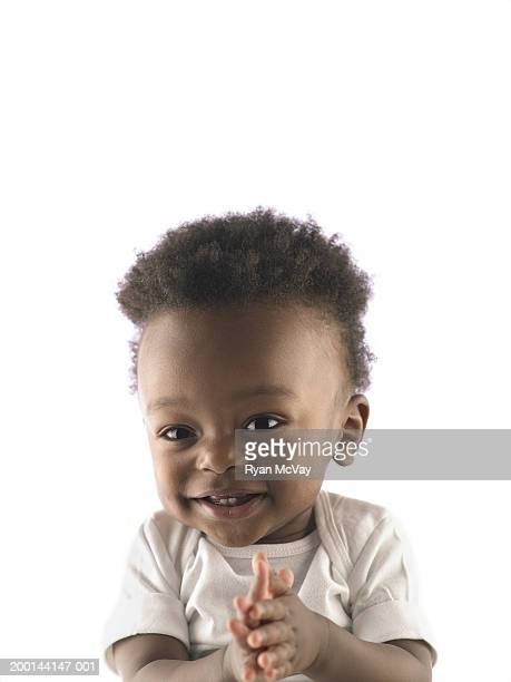 Toddler boy (9-12 months) clapping hands, portrait