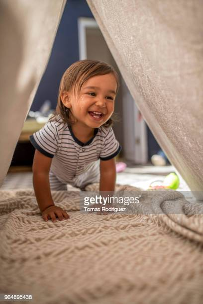 Toddler boy crawling through a tent