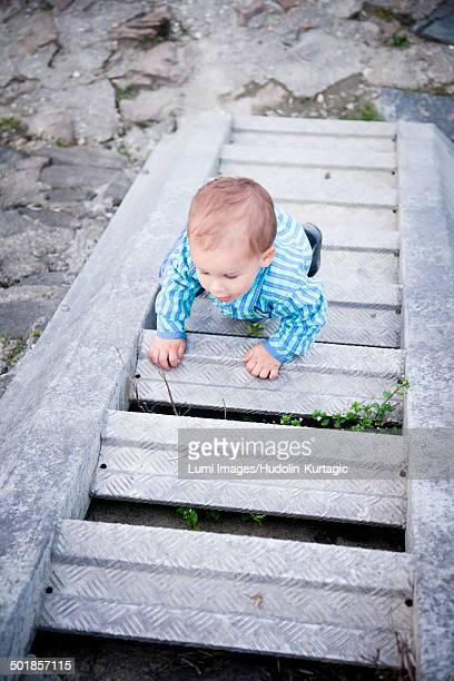 Toddler boy crawling upstairs, Austria
