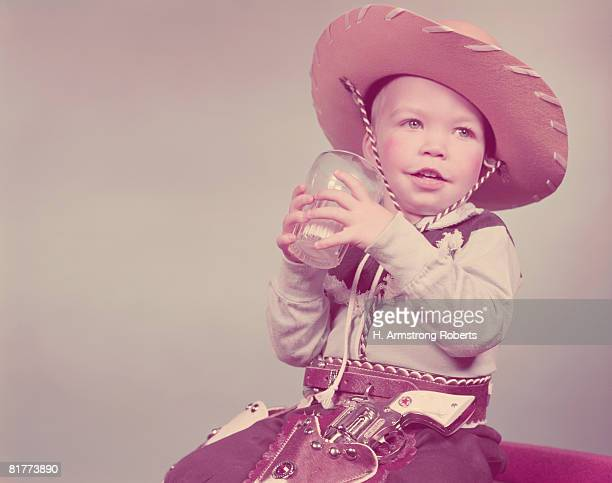Toddler boy dressed as cowboy, drinking glass of milk. (Photo by H. Armstrong Roberts/Retrofile/Getty Images)