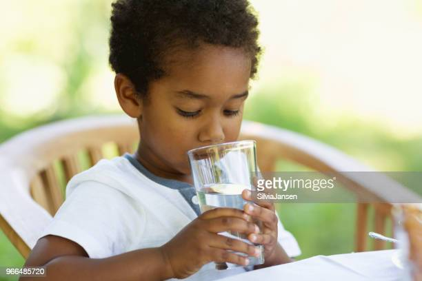 Toddler boy drinking a glass of water