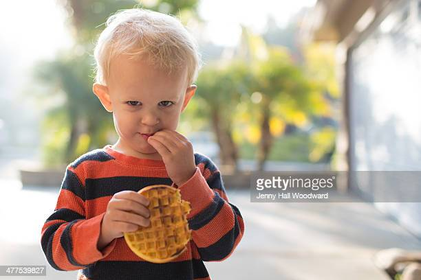 toddler boy eating a frozen waffle - laguna niguel stock pictures, royalty-free photos & images