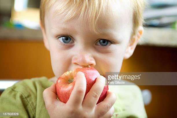 Toddler boy eating apple