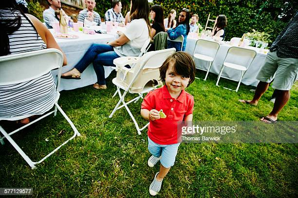 Toddler boy eating cookie during birthday party