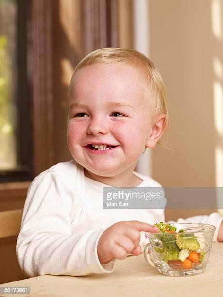 Toddler boy eating vegetables