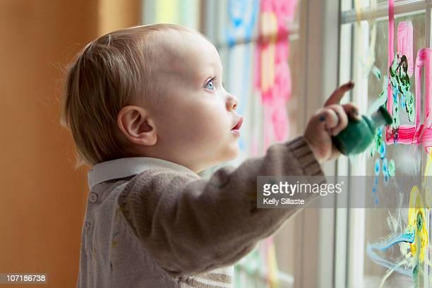 A toddler boy enjoying window painting
