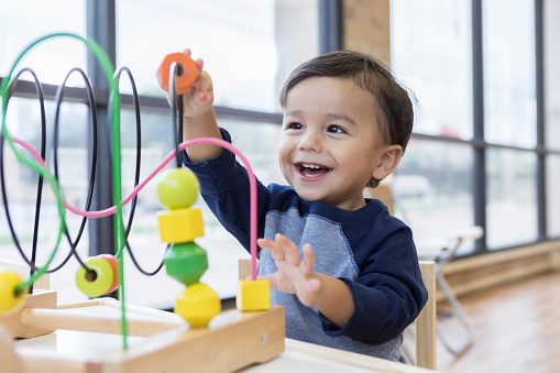 Toddler boy enjoys playing with toys in waiting room 1056360056
