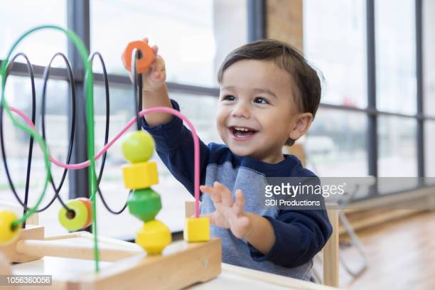 toddler boy enjoys playing with toys in waiting room - boys stock pictures, royalty-free photos & images