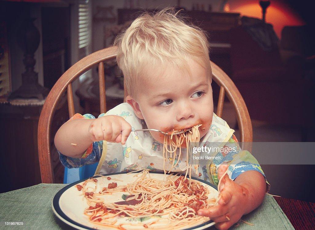 Toddler boy feeding himself spaghetti : Stock Photo