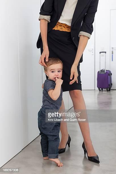 Toddler boy greeting mother in hallway
