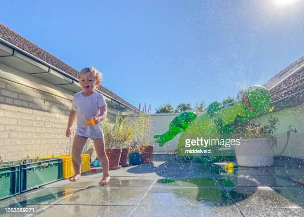 de jongen die van de peuter de pret van het water heeft - actieve levenswijze stockfoto's en -beelden
