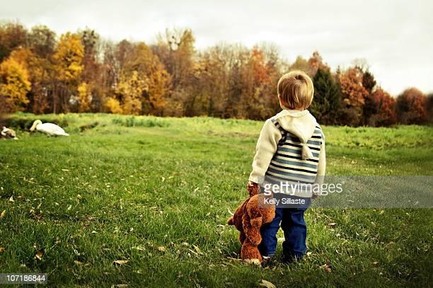 A toddler boy holding his teddy bear