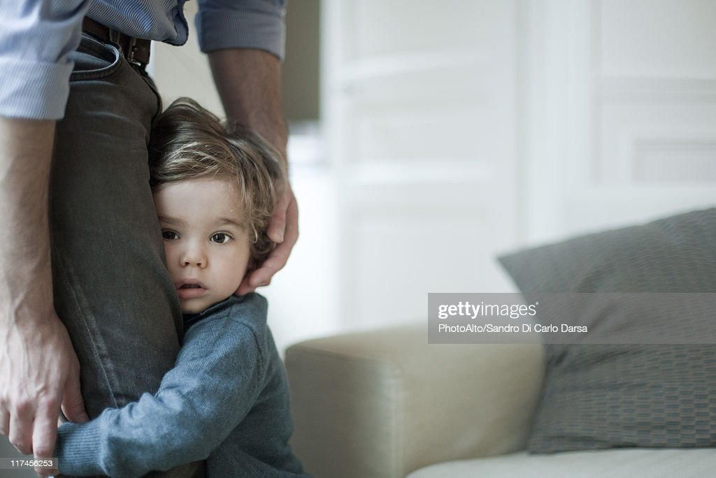 Toddler boy holding on to father's legs : Stock Photo