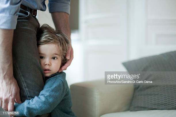 Toddler boy holding on to father's legs
