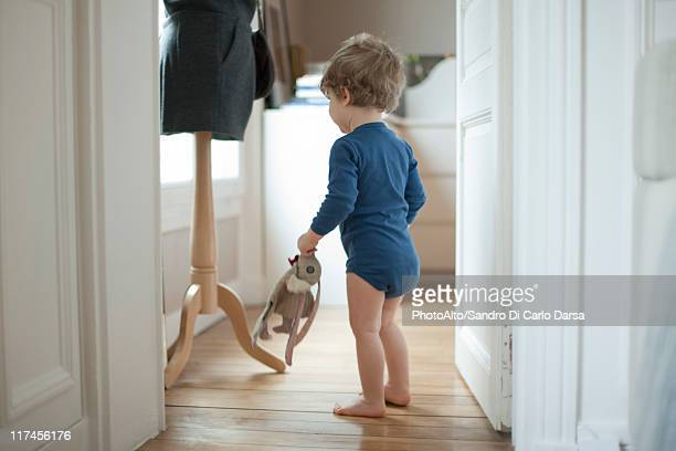 Toddler boy holding toy at home, rear view