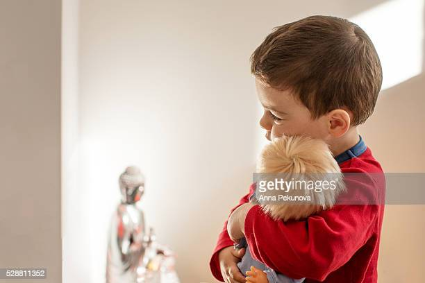 Toddler boy hugging a doll