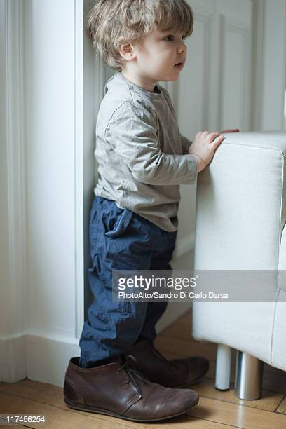 Toddler boy in father's shoes, portrait