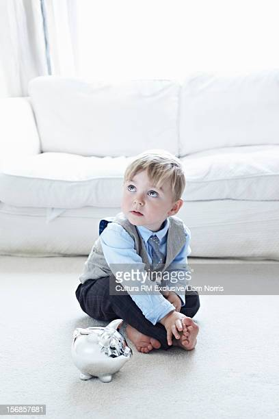 Toddler boy in suit with piggy bank
