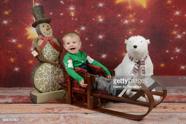 Toddler boy (2 yrs) in Xmas sweaters laughing sitting on wooden sled, with snowman and plush polar bear