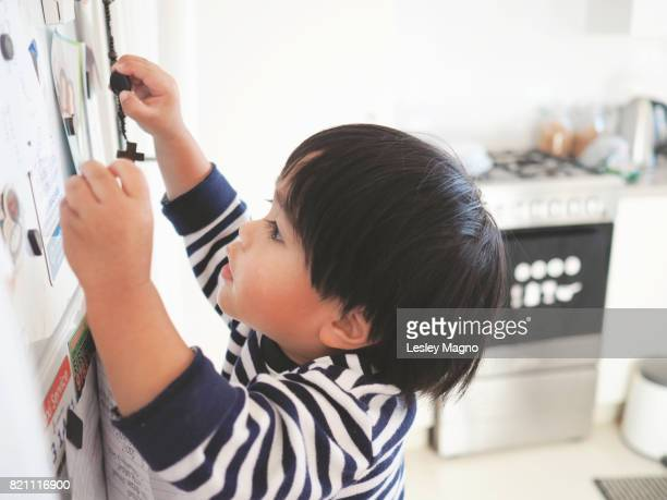 Toddler boy is playing with magnets on their refrigerator