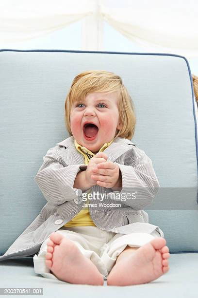Toddler boy (12-15 months) laughing in arm chair, close-up