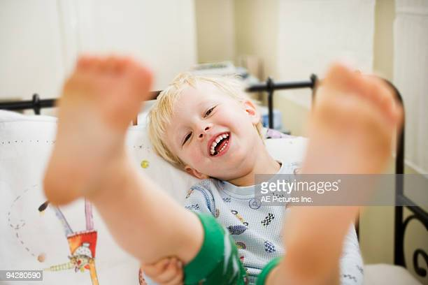 Toddler boy lays in bed with feet up